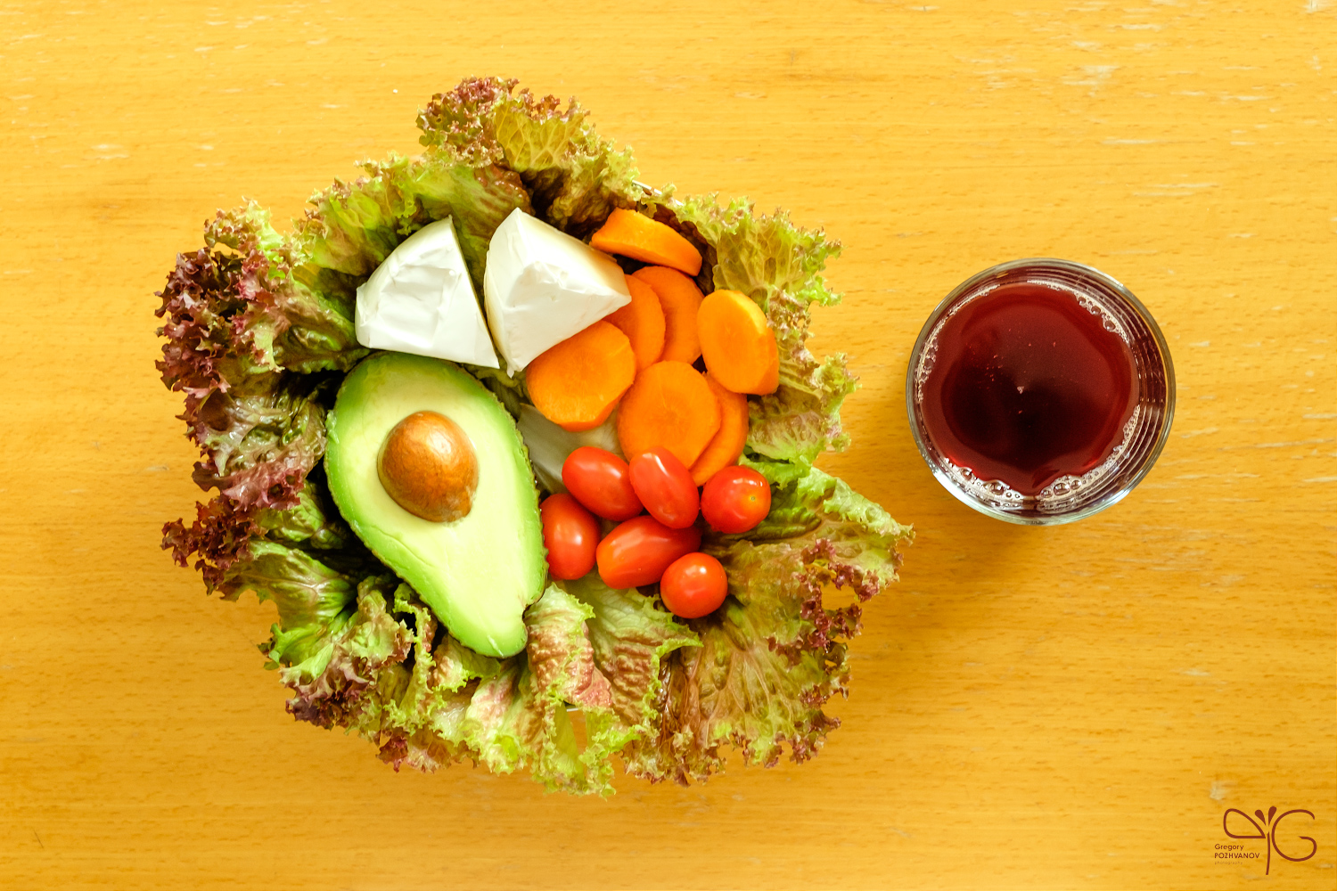 Vegetarian lunch meal served on a dish with glass of grape juice, containing salad leaves, camembert cheese, avocado, carrot and cherry roma tomatoes