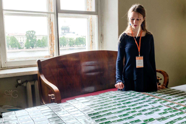 Valeria Dmitrieva stands behind a registration desk filled with participant badges